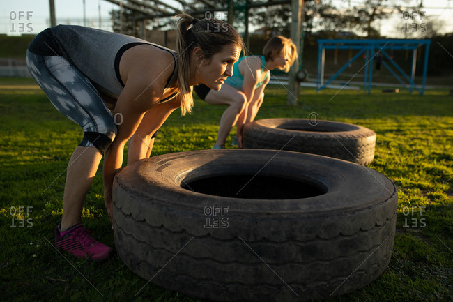 Side view of two young Caucasian women flipping tires at an outdoor gym during a bootcamp training session