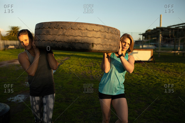 Front view of two young Caucasian women carrying a tire at an outdoor gym during a bootcamp training session