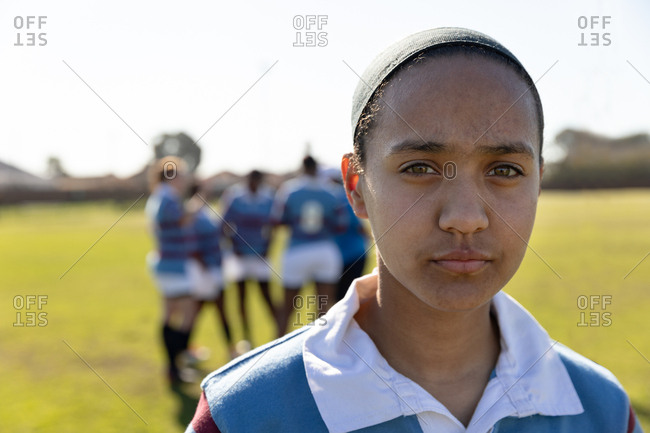 Portrait close up of a young adult mixed race female rugby player standing on a rugby pitch looking to camera, with her teammates talking together in the background