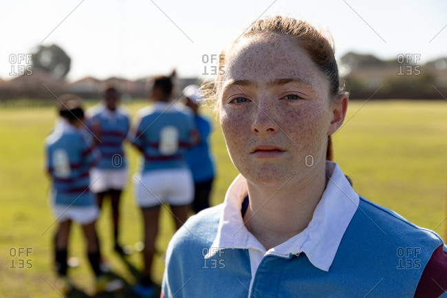 Portrait close up of a young adult Caucasian female rugby player standing on a rugby pitch looking to camera, with her teammates talking together in the background