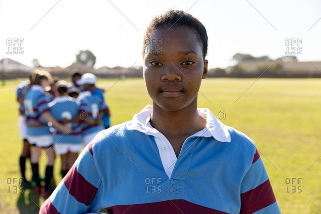 Portrait close up of a young adult mixed race female rugby player standing on a rugby pitch looking to camera, with her teammates in a huddle together in the background