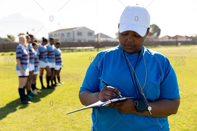 Front view close up of a middle aged mixed race female rugby coach standing on a rugby pitch writing on a clipboard, with her team standing in a row together in the background
