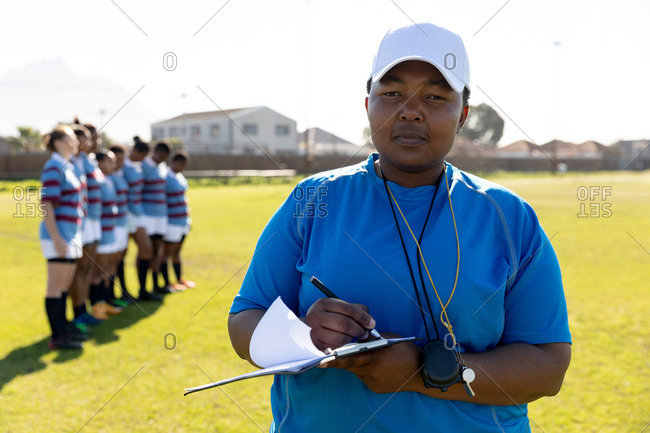 Front view close up of a middle aged mixed race female rugby coach standing on a rugby pitch writing on a clipboard and looking to camera, with her team standing in a row together in the background