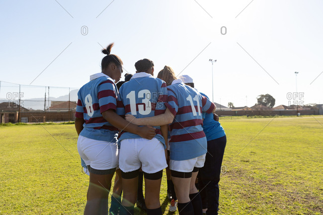 Rear view of a team of young adult multi-ethnic female rugby players and their coach standing in a huddle on a rugby field preparing for a rugby match