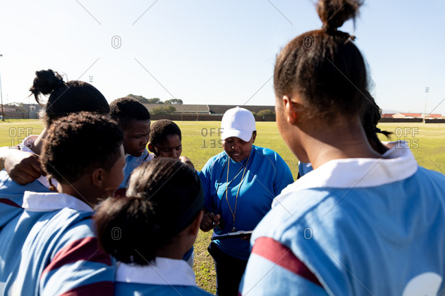 Rear view of a team of young adult multi-ethnic female rugby players standing on a rugby field with arms linked listening to their middle aged mixed race female coach while preparing for a rugby match