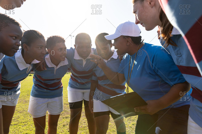 Side view of a team of young adult multi-ethnic female rugby players standing on a rugby field with arms linked in a huddle listening to their middle aged mixed race female coach while preparing for a rugby match
