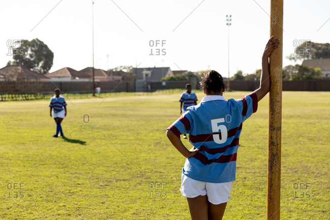 Rear view of a young adult mixed race female rugby player standing on a rugby field leaning on a goal post, with her teammates in the background