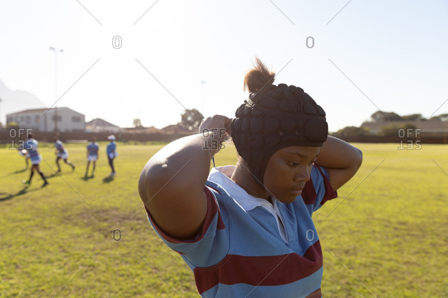 Side view close up of a young adult mixed race female rugby player standing on a rugby pitch fastening her headguard, with her teammates in the background