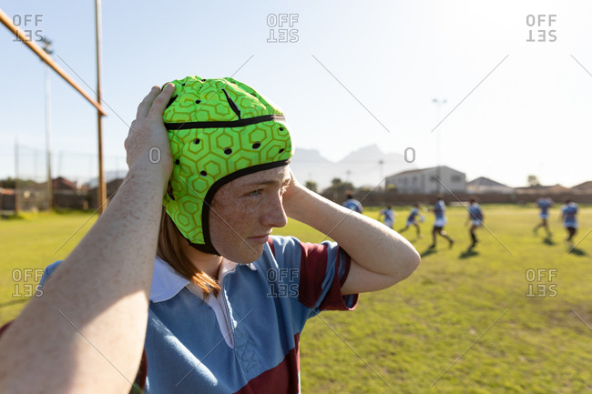 Side view close up of a young adult Caucasian female rugby player standing on a rugby pitch fastening her headguard, with her teammates in the background