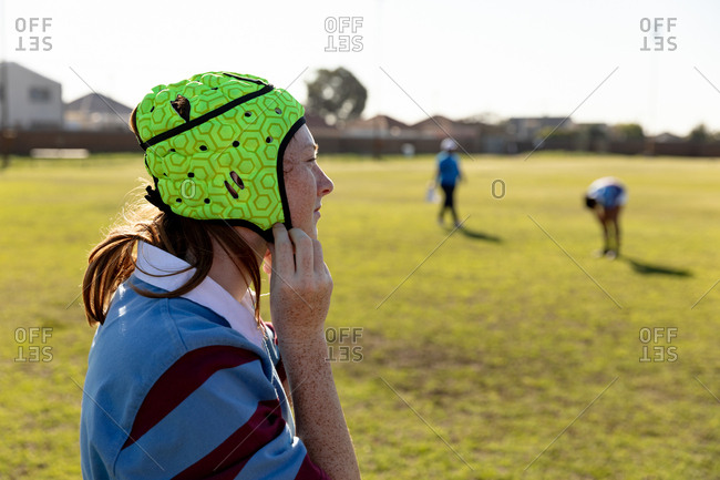 Side view of a young adult Caucasian female rugby player standing on a rugby pitch fastening her headguard, with her teammates in the background