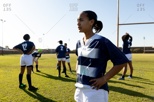 Front view of a young adult mixed race female rugby player standing on a rugby pitch with her hands on her hips looking away, with her teammates stretching in the background