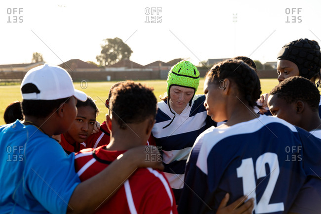 Rear view close up of young adult multi-ethnic female rugby players and their middle aged mixed race female coach standing in a huddle on a rugby field during a match