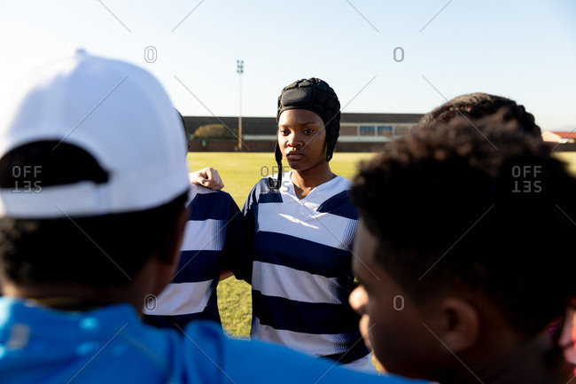 Over the shoulder view of a team of young adult multi-ethnic female rugby players and their coach standing in a huddle on a rugby field with arms linked preparing for a rugby match