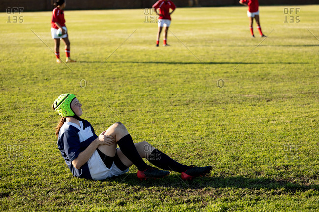 Side view of a young Caucasian female rugby player wearing a headguard sitting on a rugby pitch holding her injured leg, with other players in the background