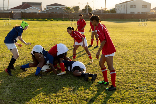 Side view of a group of young adult multi-ethnic female rugby players during a match, with one player tackled to the ground and others grabbing for the ball