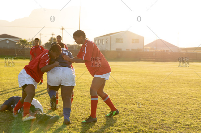 Side view of two young adult mixed race female rugby players tackling a player from the opposing team during a rugby match, with other players in the background and one lying on the ground
