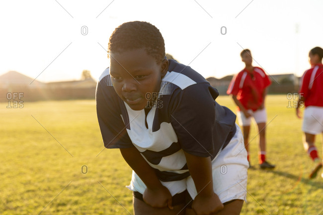 Front view close up of a young adult African American female rugby player taking a break on a rugby pitch to recover after a match, with players from the other team in the background