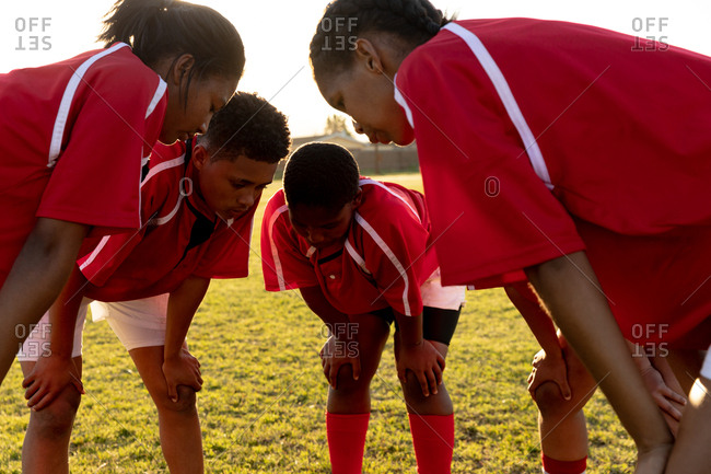 Side view of a team of young adult multi-ethnic female rugby players standing in a huddle on a rugby pitch relaxing after a rugby match