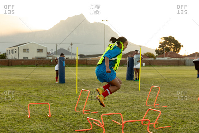 Side view of a young adult mixed race female rugby player jumping over agility hurdles on a rugby field during a training session, with teammates in the background