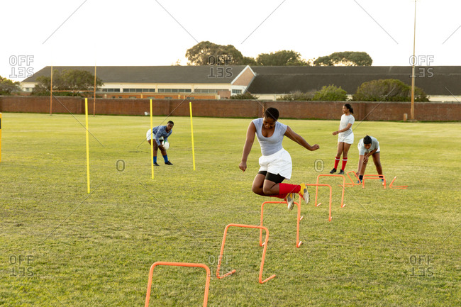 Front view of a young adult mixed race female rugby player jumping over agility hurdles on a rugby field during a training session, with teammates in the background