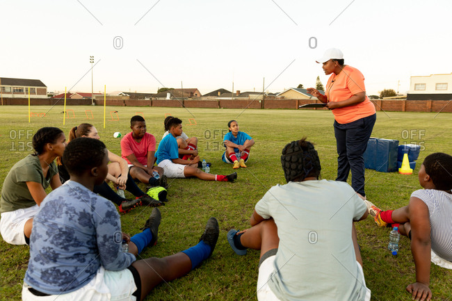 Mixed race female rugby coach holding a clipboard and talking to a team of a young adult multi-ethnic female rugby players sitting on a field during a training session