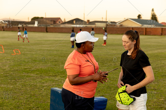 Side view of a middle aged mixed race female rugby coach talking to a young adult Caucasian female rugby player at a sports field during a training session