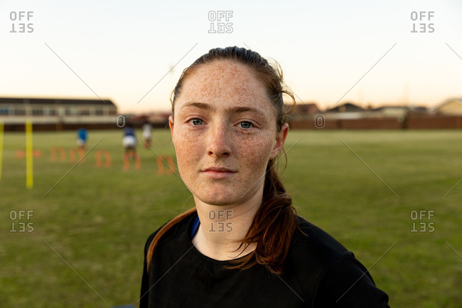 Portrait close up of a young adult Caucasian female rugby player standing on a rugby pitch looking to camera, with her teammates training in the background