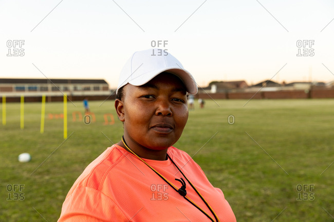 Portrait close up of a middle aged mixed race female rugby coach standing on a sports field looking to camera smiling