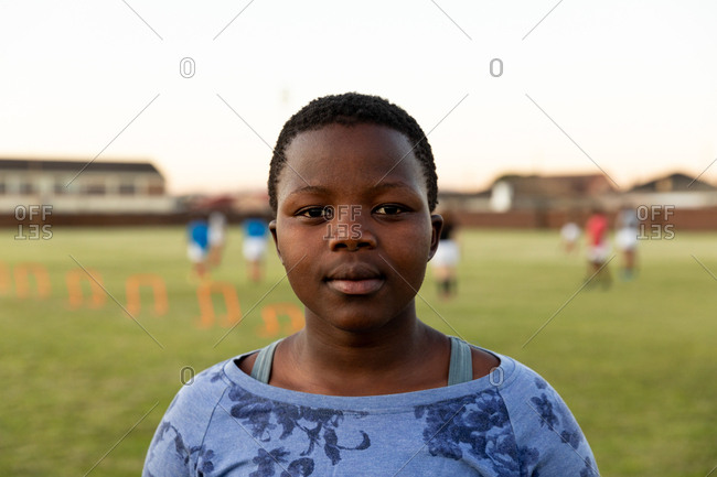 Portrait close up of a young adult African American female rugby player standing on a sports field looking to camera, with her teammates in the background