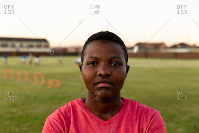 Portrait close up of a young adult African American female rugby player standing on a sports field looking to camera
