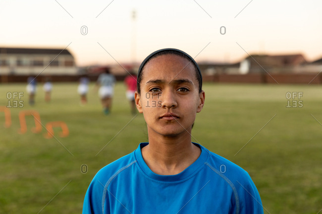 Portrait close up of a young adult mixed race female rugby player standing on a rugby pitch looking to camera, with her teammates in the background