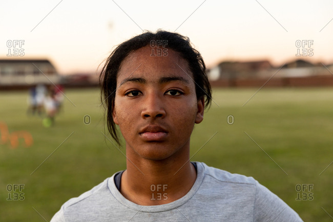 Portrait close up of a young adult mixed race female rugby player standing on a rugby pitch looking to camera, with her teammates training in the background