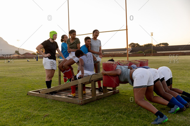 Side view of a team of a young adult multi-ethnic female rugby players on a sports field at a training session, with three of the young women practicing with a scrum machine while the others watch