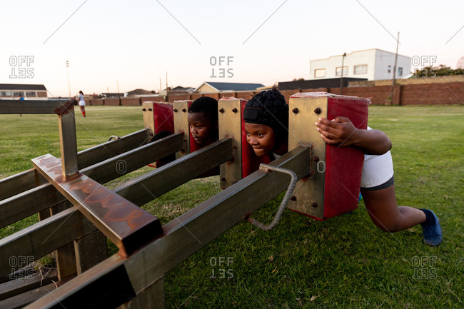 Front view of two young adult African American female rugby players using a scrum machine on a rugby pitch during a team training session