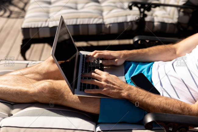 Side view mid section of a young Caucasian man relaxing on holiday, reclining on a sun lounger and using a laptop computer
