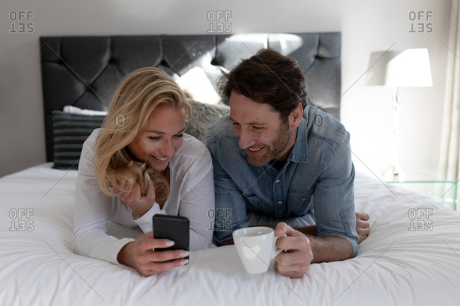 Front view of a happy young Caucasian couple relaxing together on holiday in a hotel room lying on a bed using a smartphone