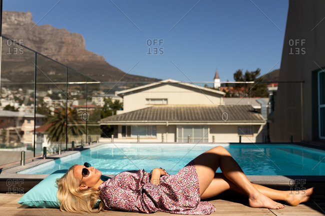 Side view of a happy young Caucasian woman relaxing on holiday lying by a swimming pool