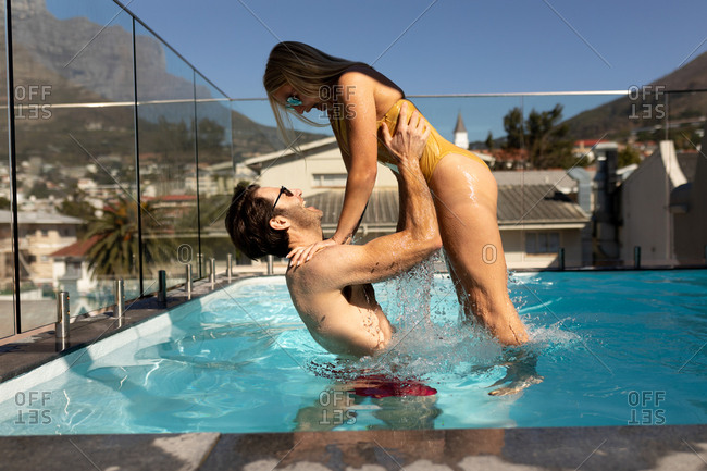 Side view of a happy young Caucasian couple relaxing on holiday in a swimming pool, the man holding the woman in the air