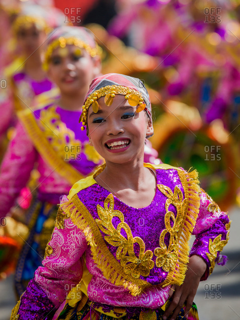 Davao, Philippines - November 13, 2018: Young girl performing in the parade at the annual Kadayawan Festival wearing a colorful costume