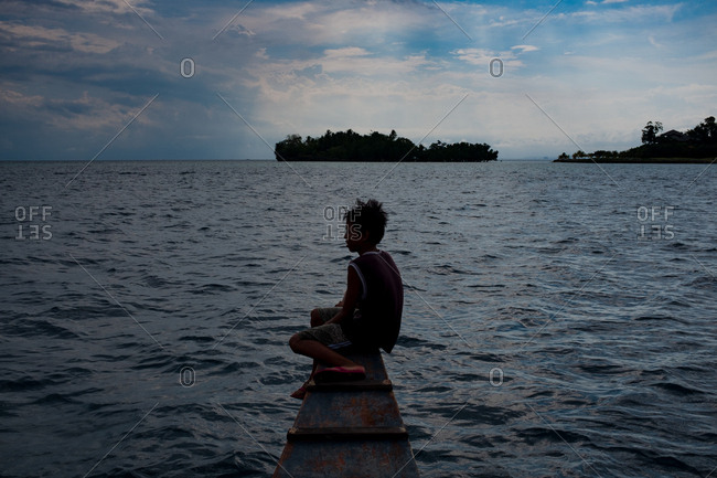 Davao, Philippines - November 13, 2018: A boy surveys the sea aboard a boat in Davao, Philippines