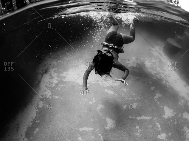 Underwater view of girl swimming in pool in black and white