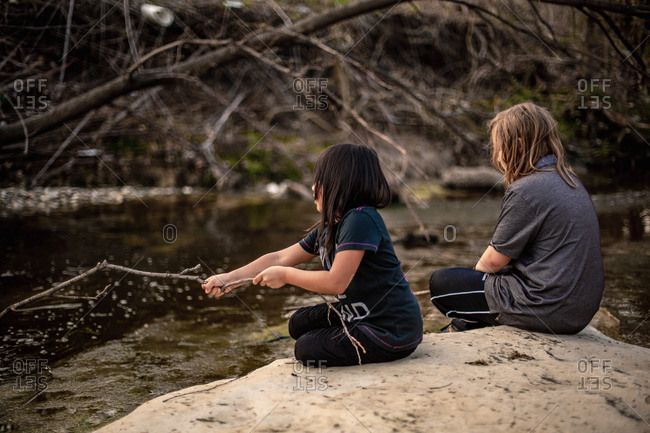 Two kids sitting on rock playing with sticks by river