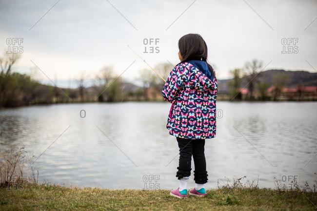 Little girl with fishing pole on lakeshore