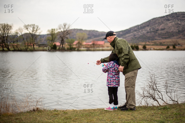 Dad teaching daughter how to fish on a lake