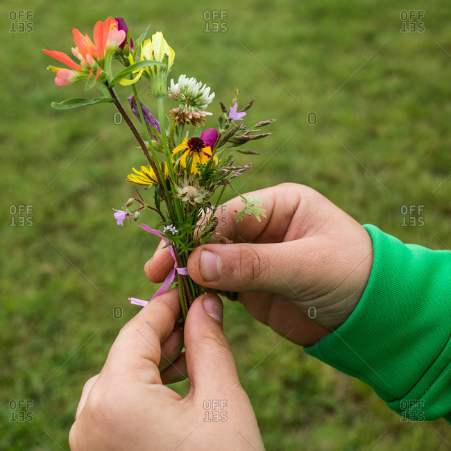 Child holding small arrangement of colorful flowers