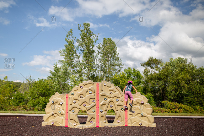 Rear view of little girl climbing on play rock wall at park