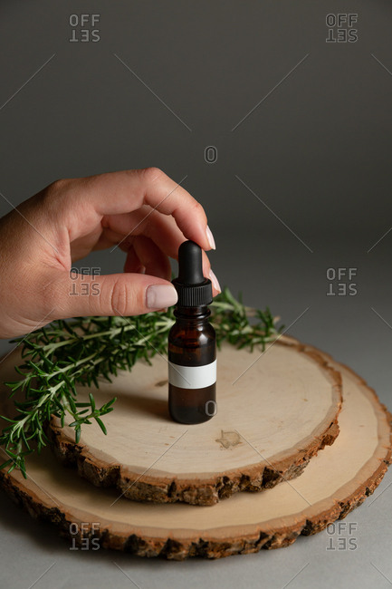 Woman placing dropper into essential oil bottle surrounded by rosemary