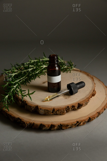 Brown bottle with essential oil surrounded by rosemary