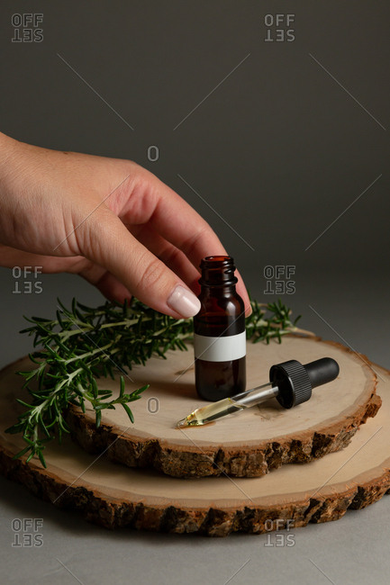 Hand holding a bottle with essential oil surrounded by rosemary