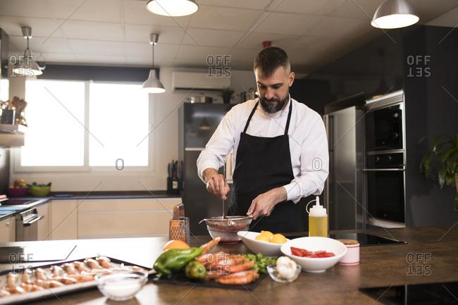 Bearded chef preparing sauce in kitchen